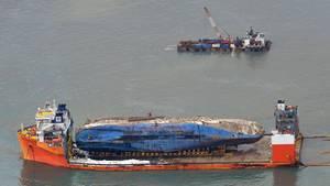 Auf der Ladefläche eines Transportschiffes liegt das Wrack der geborgenen Fähre Sewol auf dem Weg in einen Hafen in Südkorea