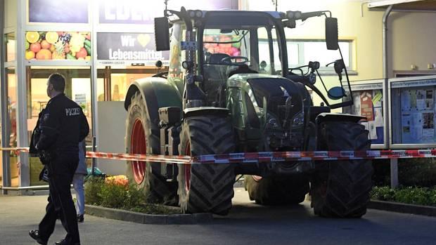 Ein Traktor steht in Köln-Esch vor einem Supermarkt. Vier Räuber hatten es auf den Geldautomaten im Eingangsbereich abgesehen.