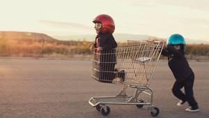 Ein Junge kniet im Einkaufswagen, ein zweiter schiebt, bei tragen einen Motorradhelm