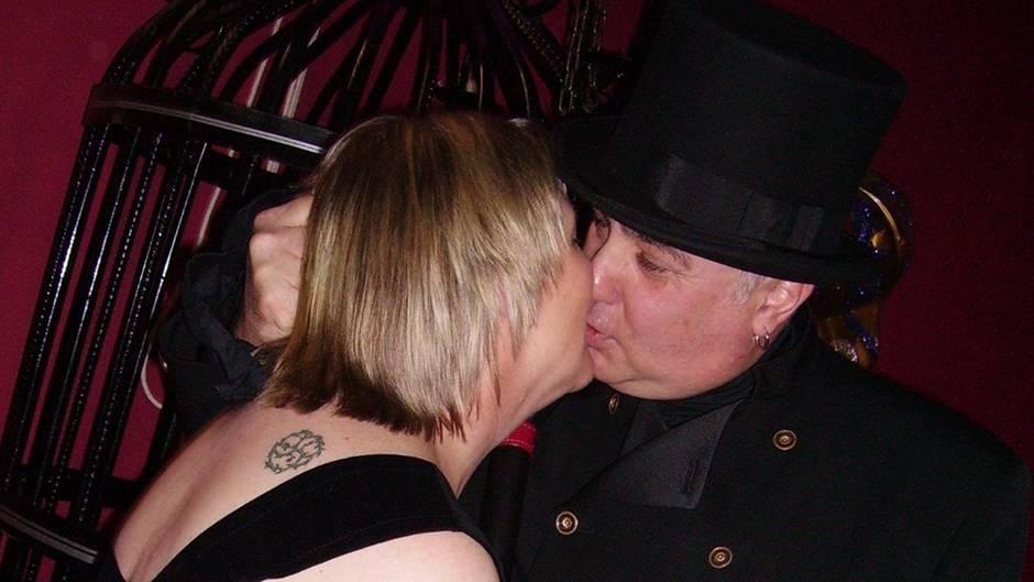 """Die australische Sex-Sklavin, ganz in schwarz gekleidet, küsst ihren """"Master Joe""""."""