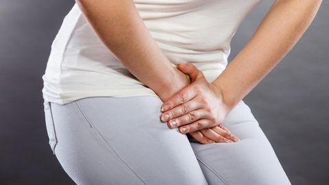 Eine Frau hat Schmerzen und fasst sich an den Bauch.