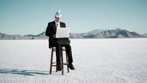 Ein Mann mit Aluhut auf einem Barhocker mit Laptop auf den Knien.