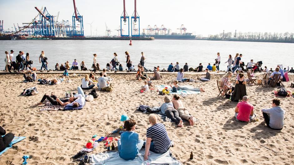 bei gutem Wetter sitzen und liegen Menschen am Hamburger Elbstrand