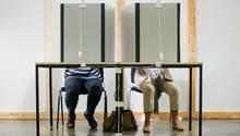 Ein Mann und eine Frau sitzen in einer Wahlkabine