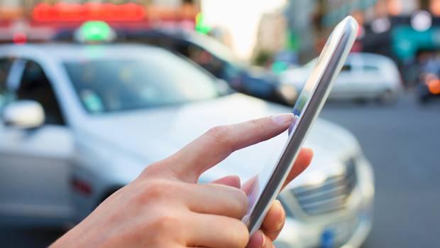 Eine Frau bestellt ein Taxi mit ihrem Smartphone