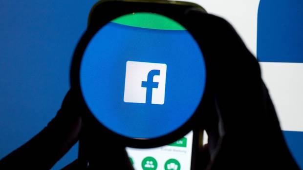 Das Facebook-Logo durch eine Lupe betrachtet