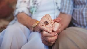 Ein älteres Ehepaar hält Händchen.