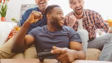 Drei Männer spielen gemeinsam an der Playstation 4