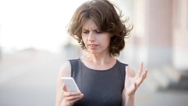 Eine Frau schaut verärgert auf ihr Smartphone