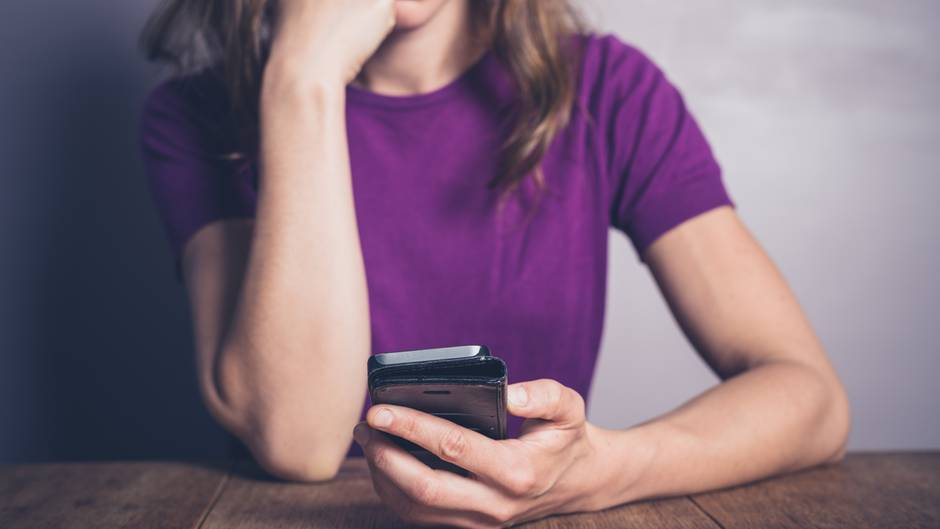 Eine Frau starrt entsetzt auf ihr Smartphone