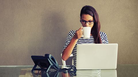 Eine Frau sitzt mit einer Kaffeetasse am Notebook