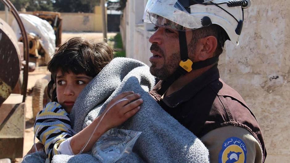 """Ein freiwillige Helfer der """"Syria Civil Defence"""" (Weißhelme) bringt ein Kind, das durch den mutmaßlichen Giftgasangriff in Chan Scheichun verletzt wurde, in Sicherheit."""