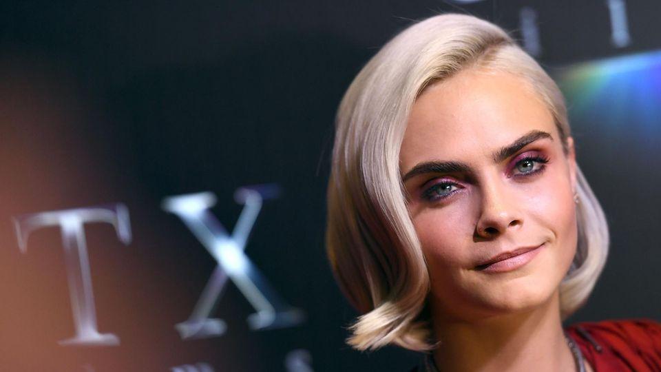 Super-Model Cara Delevignie lächelt mit blondierten Haaren und in einem roten, gerafften Oberteil in die Kamera