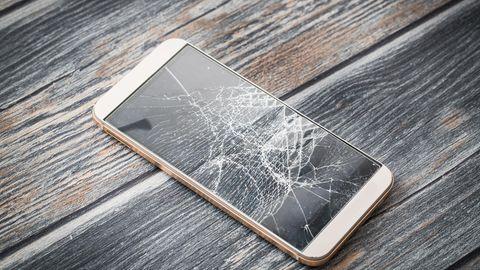 Ein Smartphone liegt mit gerissenem Display auf einem Holzboden