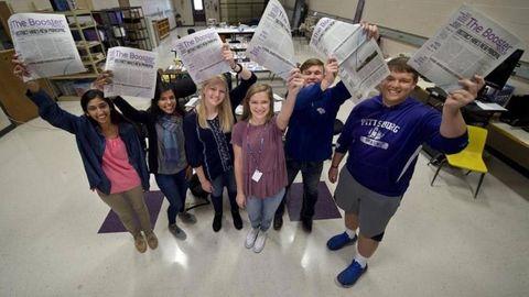 Die strahlenden Schüler zeigen ihre Zeitung