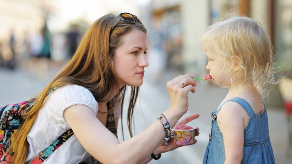Mutter füttert Tochter mit Eis