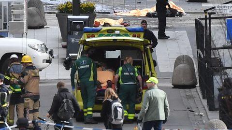 Rettungskräfte kümmern sich nach dem Lkw-Anschlag im Zentrum von Stockholm um eine verletzte Person