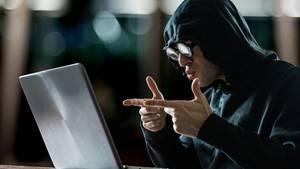 Ein lächerlich verkleideter Hacker sitzt vor einem Laptop