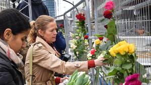 An einem Zaun, mit dem der Ort des Anschlages in Stockholm abgesperrt ist, befestigen zwei Frauen Rosen
