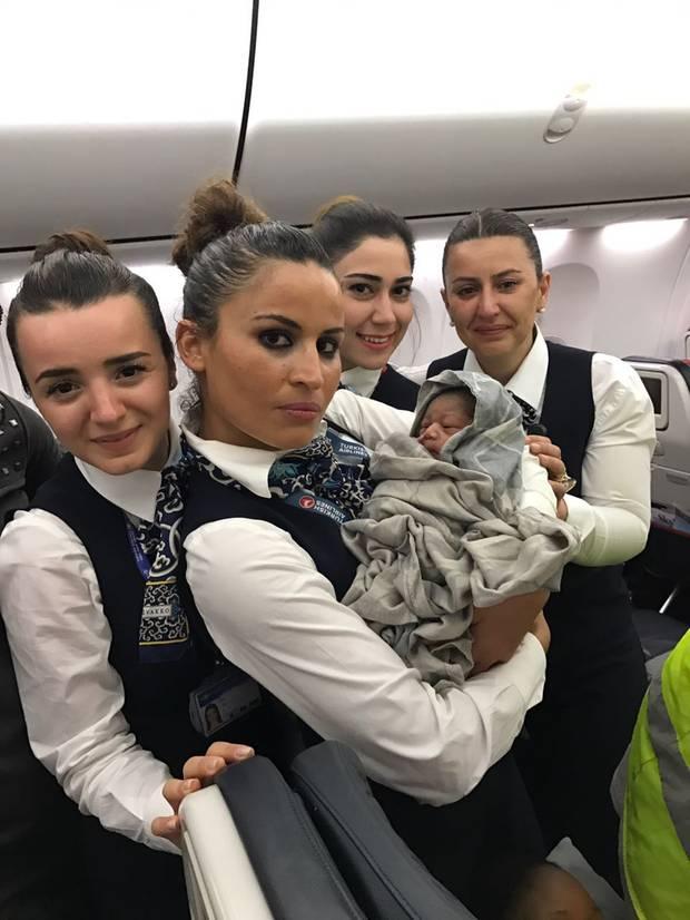 """Himmlischer Geburtsort in einem Flugzeug: Die Flugbegleiter halten die kleine in Decken gewickelte """"Kadiju"""" im Arm."""