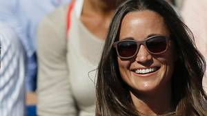 Pippa Middelton sitzt in weiß-rosa geblümten Oberteil und mit Sonnenbrille auf der Tribüne bei einem Tennisturnier