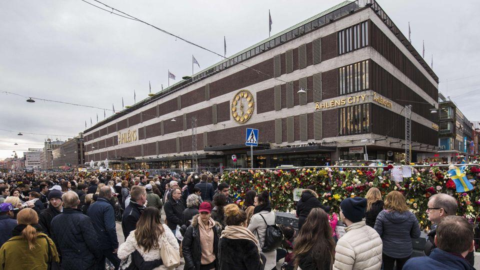 Passanten trauern vor dem Kaufhaus Ahlens City in Stockholm