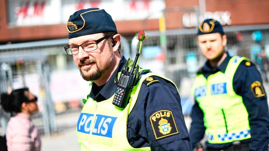 Polizisten in Stockholm tragen Rosen an der Uniform