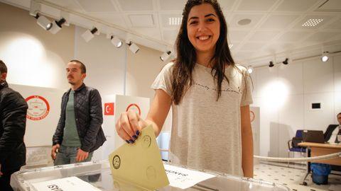 Eine junge Frau gibt in einem Wahlbüro in Warschau, Polen, ihren Stimmzettel zum Referendum der Türkei ab