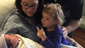 Mädchen zeigt einem Baby den Mittelfinger