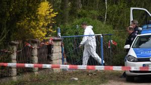 Ein Mann im weißen Overall betritt den Tatort in Borkheide - Polizisten warten vor dem Gartentor