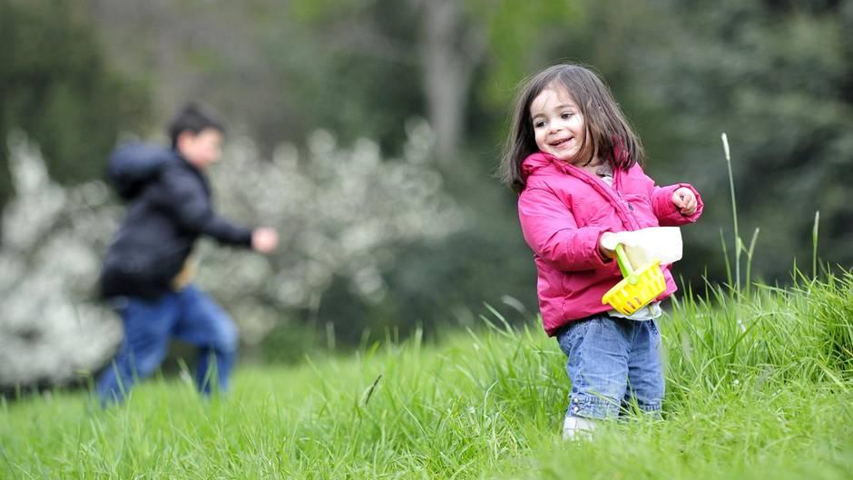 Zwei Kinder suchen auf einer Wiese Ostereier. Das Wetter an Ostern 2017 wird ungemütlich.