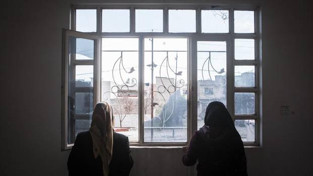 Zu sehen sind zwei Frauen, die aus einem Fenster gucken.