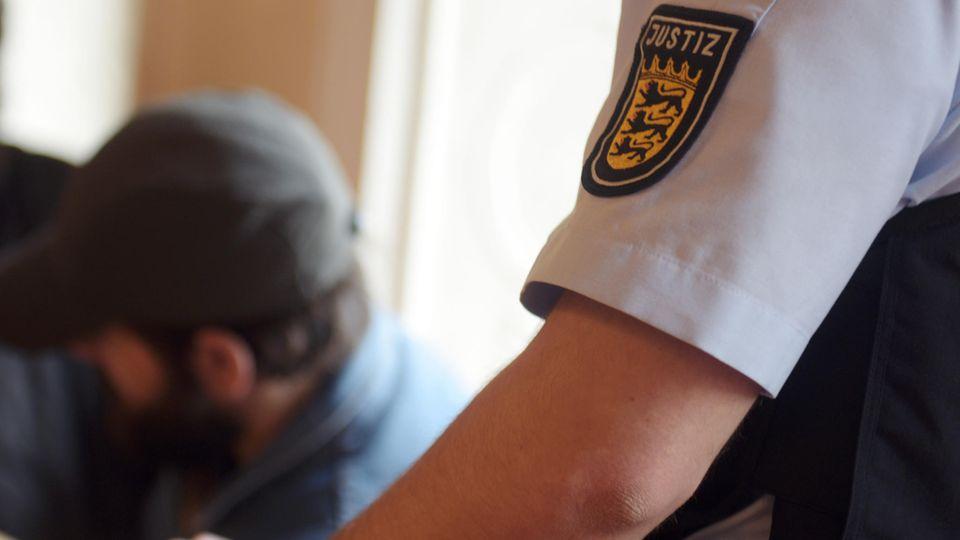 Mit Vollbart und ins Gesicht gezogener Schiebermütze sitzt der 37-jährige Angeklagte im Landgericht Ellwangen