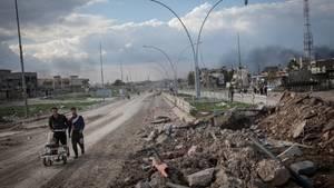 Zu sehen sind zwei Männer und ein Kind auf einer erdigen Straße, daneben ein großer Trümmerhaufen.