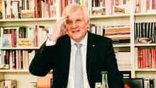 Zu sehen ist Horst Seehofer an einem Tisch mit Getränken und Gebäck. Er fasst sich amüsiert an den Kopf.