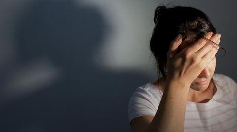 Frau hält sich vor Schmerz die Hand an den Kopf