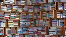 Zu sehen ist ein großes Bücherregal, aus Holzkisten gezimmert und voller Bücher.