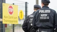 Zwei Polizisten in Kampfmontur gehen bei Borussia Dortmund am Schild vorbei, das das Betreten des Trainingsgeländes verbietet