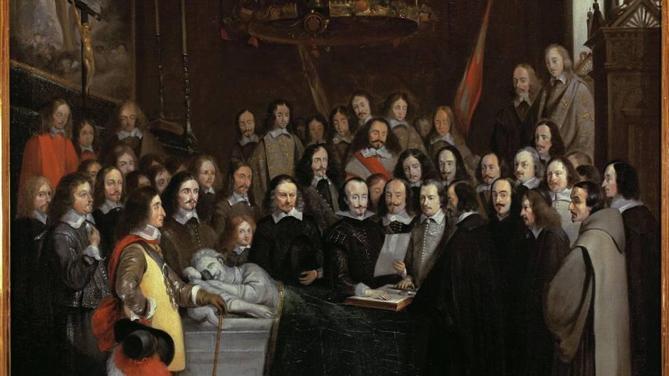 Zu sehen ist ein Gemälde aus dem 17. Jahrhundert: eine Versammlung von Diplomaten zur Vertragsunterzeichung.