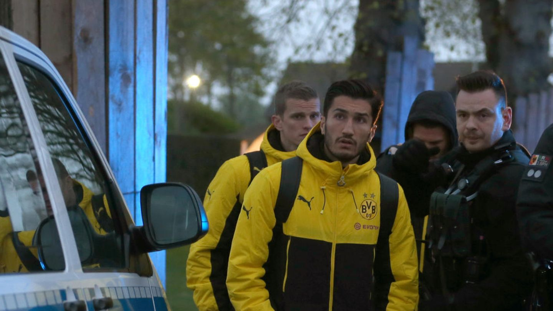 BVB-Spieler Nuri Sahin steht in Teamkleidung zwischen einem Poliziebus und bewaffneten Polizisten
