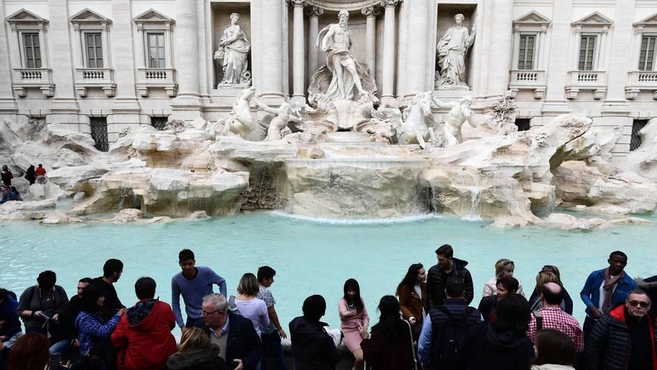 Touristen stehen vor dem Trevi-Brunnen in Rom