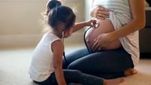 Mädchen betastet den Bauch ihrer schwangeren Mutter
