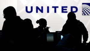 Vor einem Schalter von United Airlines zeichnen sich die dunklen Konturen von Flugpassagieren ab