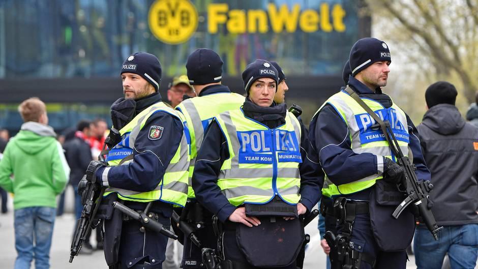Fünf Polizistinnen und Polizisten stehen Rücken an Rücken vor dem Stadion von Borussia Dortmund