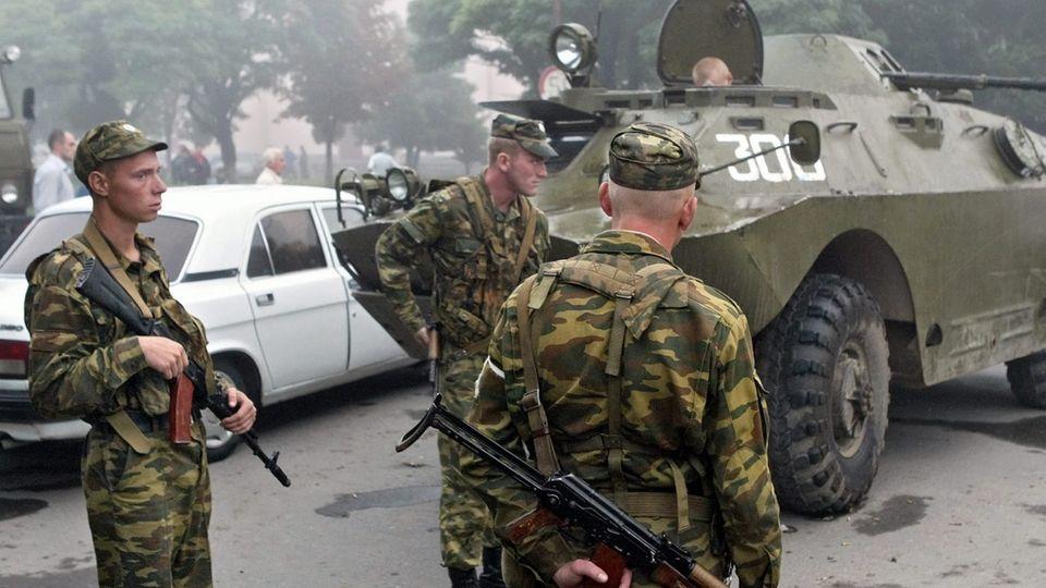 Russische Soldaten stehen am 1. September 2004 nahe der Grundschule in Beslan, in der sich das Geiseldrama ereignete