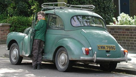 Junge steht neben einen Auto und lacht