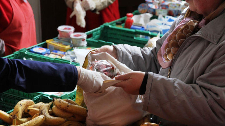 Ein Berliner Tafel-Mitarbeiter packt Obst in eine Tragetasche.