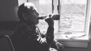 Ein alter Mann sitzt am Fenster und trinkt ein Bier aus der Flasche