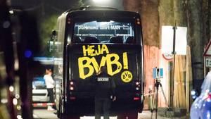 """Im Dunkeln steht der BVB-Mannschaftsbus am Ort des Anschlags, während am Heck mit """"Heja BVB!"""" ein Polizist Spuren sichert"""