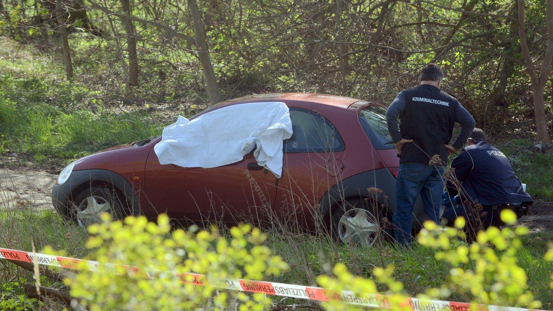 Polizisten und Mitarbeiter der Spurensicherung untersuchen das Auto